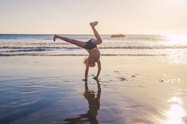 Little boy practicing handstand on the beach - IHF00320
