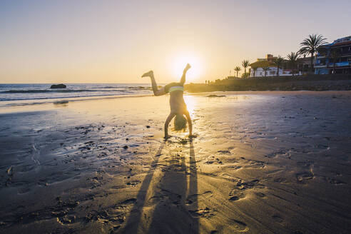 Little boy practicing handstand on the beach - IHF00329