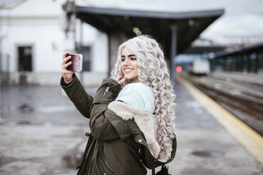 Portrait of smiling young woman taking selfie with smartphone on platform - LJF01495