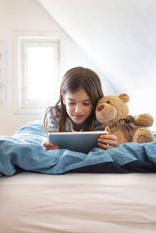 Portrait of smiling girl lying on bed with teddy bear using digital tablet - LVF08778