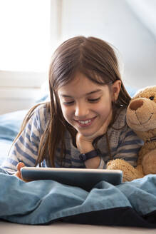 Portrait of smiling girl lying on bed with teddy bear using digital tablet - LVF08781