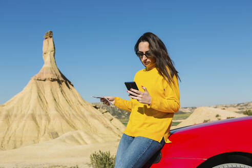 Woman looking at cell phone in desertic landscape of Bardenas Reales, Arguedas, Navarra, Spain - XLGF00001