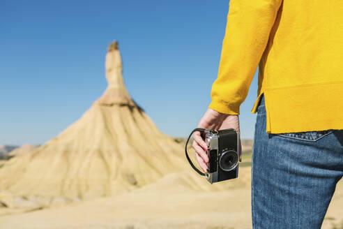 Woman holding a vintage camera in desertic landscape of Bardenas Reales, Arguedas, Navarra, Spain - XLGF00004