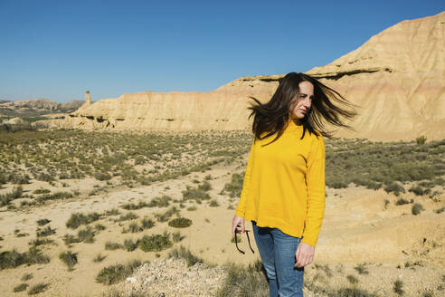 Woman shaking her hair in desertic landscape of Bardenas Reales, Arguedas, Navarra, Spain - XLGF00007
