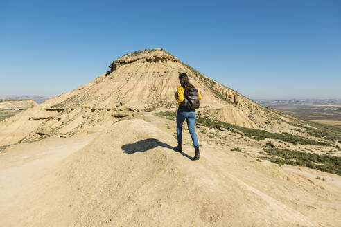 Woman walking in desertic landscape of Bardenas Reales, Arguedas, Navarra, Spain - XLGF00010
