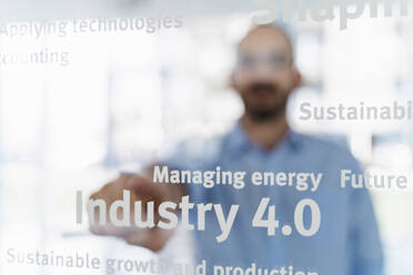 Businessman in front of glass pane pointing on words, industry 4.0 - DIGF09631