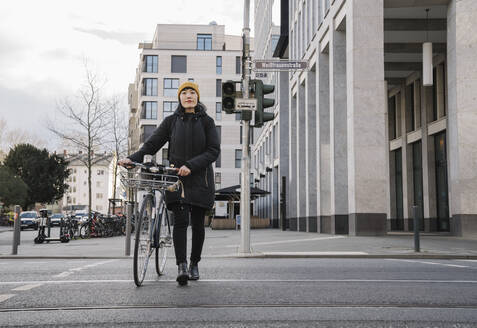 Woman with bicycle in the city on the go, Frankfurt, Germany - AHSF02212