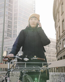 Woman with bicycle on the phone in the city, Frankfurt, Germany - AHSF02215