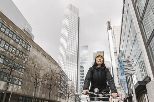 Woman riding bicycle in the city, Frankfurt, Germany - AHSF02221