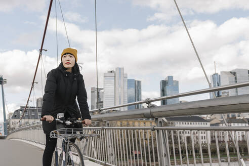 Woman riding bicycle on a bridge, Frankfurt, Germany - AHSF02233