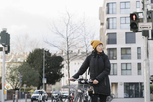 Woman with bicycle in the city, Frankfurt, Germany - AHSF02239
