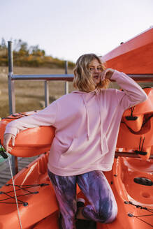 Portrait of young blond woman wearing pink hoodie sweater on jetty - AGGF00014