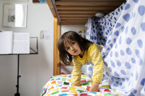 Portrait of little girl playing on bed - VABF02763