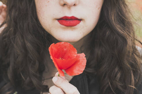 Crop view of young woman with red lips holding poppy - FVSF00101