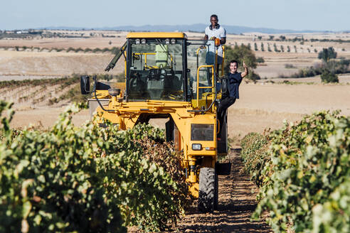 Grape harvesting machine and young winegrowers during grape harvest, Cuenca, Spain - OCMF01191