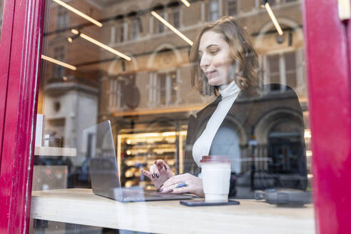 Businesswoman using laptop at a cafe in the city - WPEF02784