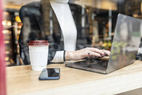 Close-up of businesswoman using laptop at a cafe in the city - WPEF02787