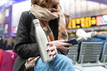 Woman sitting at train station with thermos flask and mobile phone - WPEF02799
