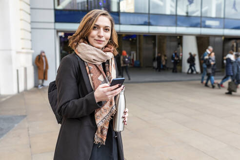 Portrait of woman with mobile phone in front of train station, London, UK - WPEF02802