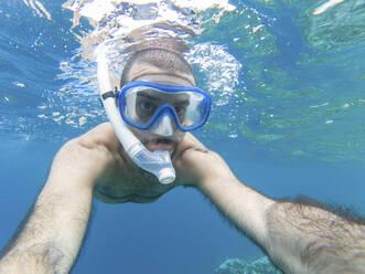 Snorkeler taking underwater selfie - WPEF02807