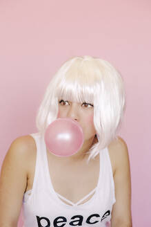 Portrait of young woman with pink gum bubble in front of pink background - ERRF03431