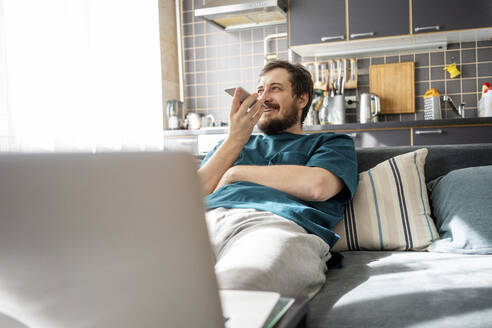 Portrait of smiling man sitting on couch at home using mobile phone - VPIF02308