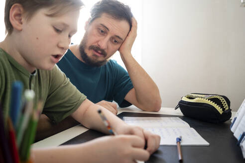 Portrait of father watching his son doing homework - VPIF02317