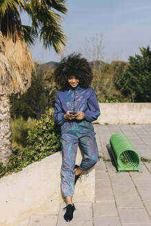 Stylish young woman wearing tracksuit and using cell phone outdoors - AGGF00021