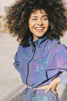Portrait of happy stylish young woman wearing tracksuit outdoors - AGGF00024
