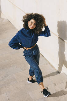 Portrait of happy stylish young woman wearing tracksuit outdoors - AGGF00027