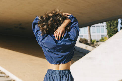 Rear view of young woman stretching outdoors - AGGF00030