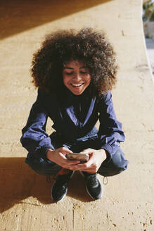 Stylish young woman wearing tracksuit and using cell phone outdoors - AGGF00033
