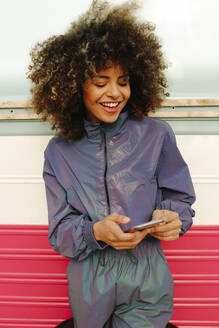 Stylish young woman wearing tracksuit and using cell phone outdoors - AGGF00036