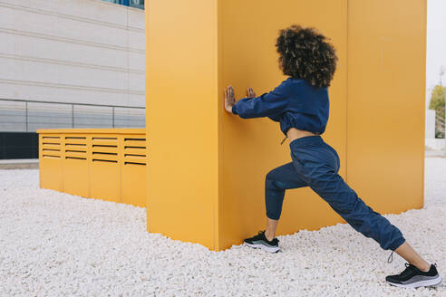 Stylish young woman doing stretching exercise at a yellow wall - AGGF00039