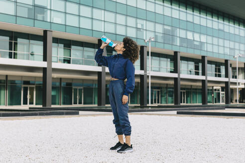 Sporty young woman having a cooling break in front of modern building - AGGF00042
