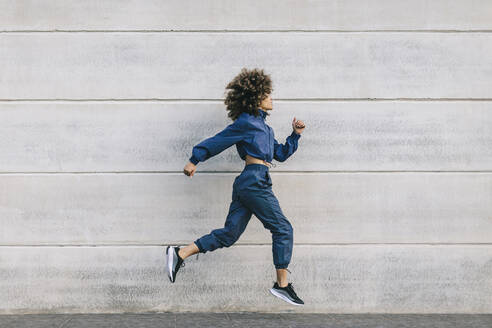 Stylish young woman running along concrete wall - AGGF00054