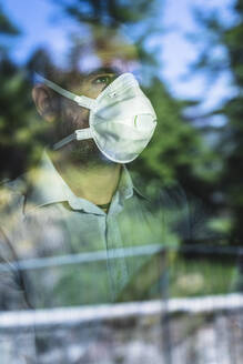 Mature pensive man with protective mask looking out of the window - MCVF00289