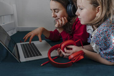 Two sisters with headphones lying on bed using laptop - OGF00272