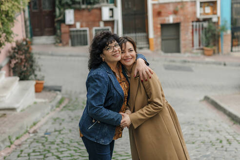 Portrait of happy mother hugging adult daughter on the street, Istanbul, Turkey - OGF00275