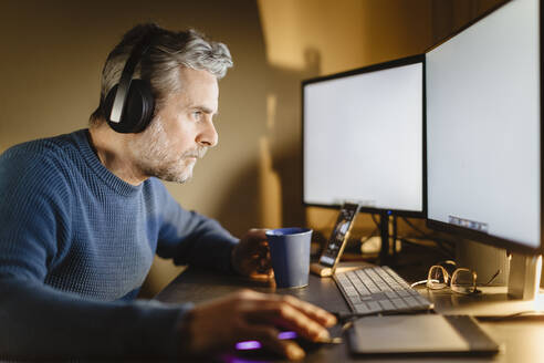 Mature man with headphones sitting at desk at home working on computer - MCVF00295