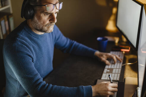 Mature man with headphones sitting at desk at home working with graphics tablet and computer - MCVF00301