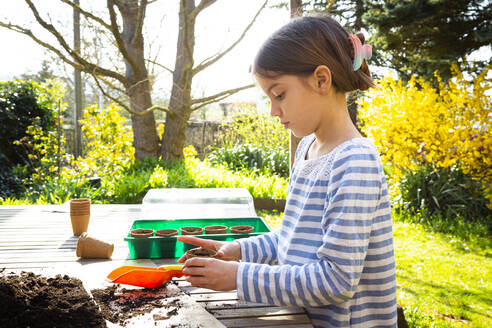 Girl filling nursery pots with soil and seeds - LVF08790