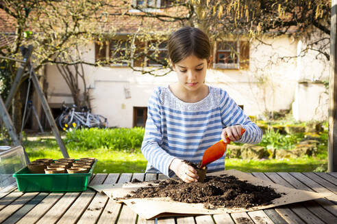 Girl filling nursery pots with soil and seeds - LVF08793