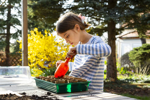 Girl filling nursery pots with soil for her little greenhouse - LVF08796