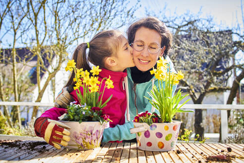 Mother and daughter planting flowers together on balcony - DIKF00448