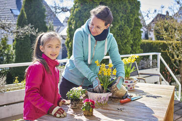 Mother and daughter planting flowers together on balcony - DIKF00451