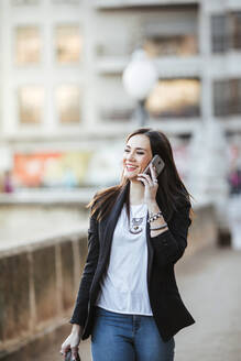 Portrait of happy woman on the phone walking in the city - LJF01504