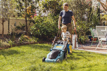 Father and son mowing the lawn together - MFF05558