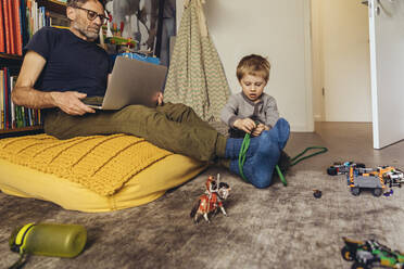 Son tying his father working on laptop in children's room - MFF05576