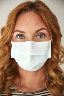 Portrait of red-haired woman wearing a protective mask at home - JHAF00073
